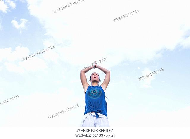 Woman doing a yoga exercise under sky with clouds