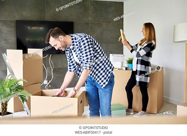 Couple moving into new flat unpacking cardboard box