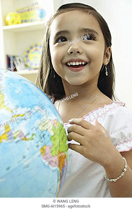 Young girl standing in front of globe, looking away