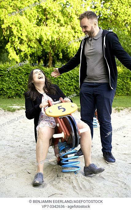 playful adult couple enjoying free time on playground, carefree, playground rocker
