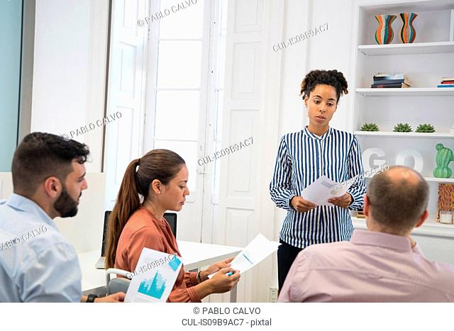 Businesswoman making graph presentation at boardroom table
