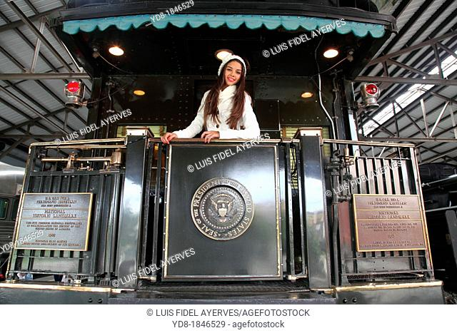 Young woman posing in the presidential train at the Gold Coast Railroad Museum, Miami, Florida, USA