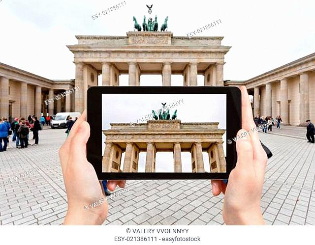 travel concept - tourist takes picture of Brandenburg gate in Belin in cloudy autumn day on Pariser Platz on tablet pc