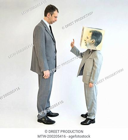 Boy wearing mask arguing with businessman
