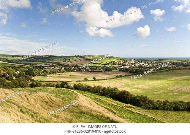 View of coastal farmland and village, with sea in distance, Preston, Dorset, England, september