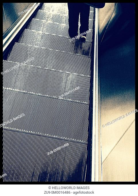 Legs of person descending on elevator, London, England, Europe