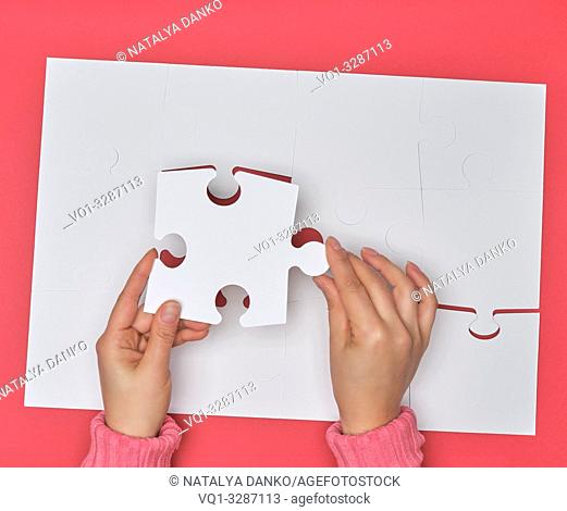 female hand puts white big puzzles on a pink background, one element missing, top view