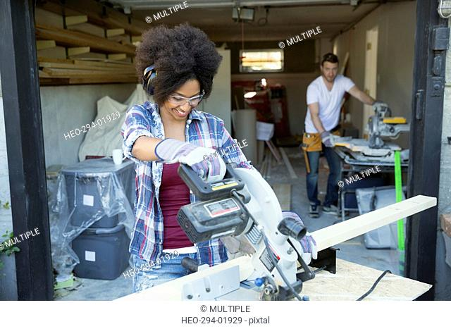 Woman using table saw for home improvement project outside garage