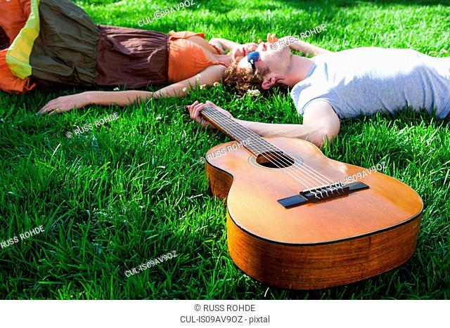 Romantic young couple lying on garden lawn