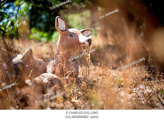 Deer figurine in field