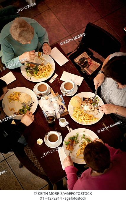 Overhead view of four people eating lunch at SALT cafe bar Aberystwyth Wales UK
