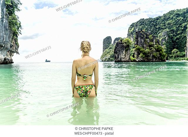 Thailand, Ko Hong, back view of woman standing in the sea looking to horizon