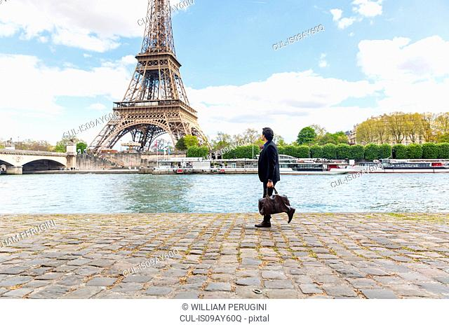 Young man walking beside river, carrying sports bag, Eiffel Tower in background