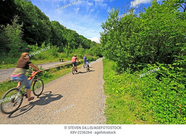 A family cycle on the Monsal Trail through Upperdale, Derbyshire, Peak District National Park, England, UK
