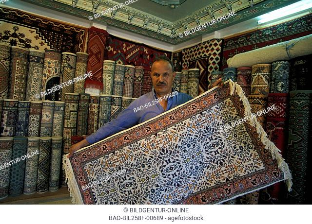 A carpet dealer in the market or Souq in the Old Town in Sousse at the Mediterranean Sea in the north-east of Tunisia in North Africa
