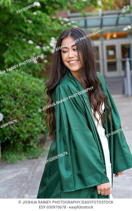 Beautiful college senior girl poses for graduation photos during the Spring on a university campus during the Spring in Oregon