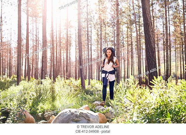Smiling young woman with backpack hiking in sunny woods