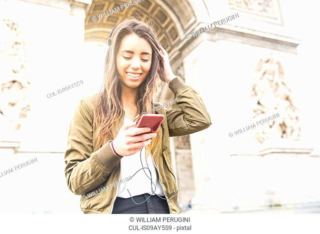 Young woman with smartphone listening to headphones at Arc de Triomphe, Paris, France
