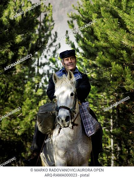 A villager rides a white horse through the forest in southwestern Serbia
