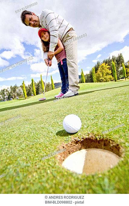Hispanic man teaching girl to play golf