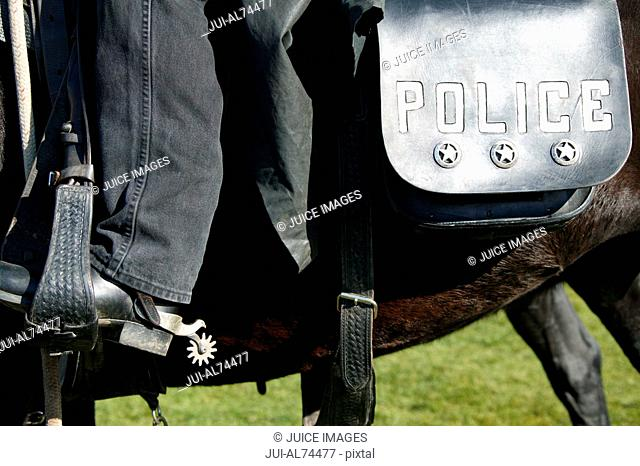Detail view of a boot, spur, and saddlebag on a horse ridden by a policeman