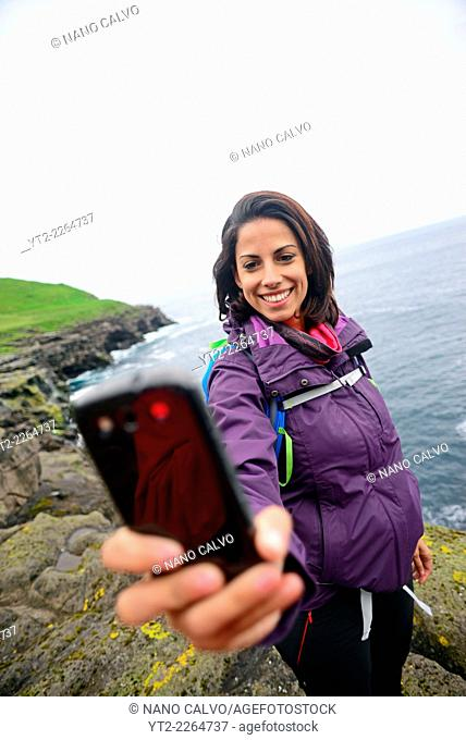 Young woman takes a selfie in Trøllanesi, Kalsoy, Faroe Islands