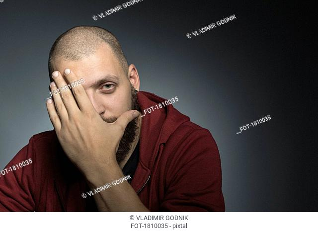 Portrait man covering face with hand