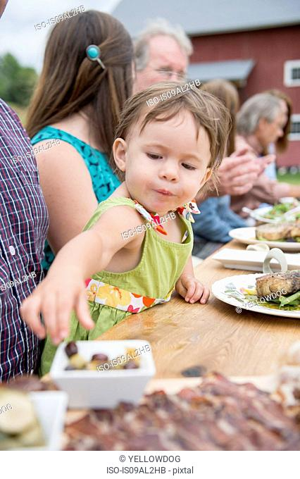 Young child picking olive from dish at family meal, outdoors