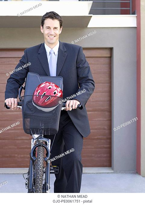 Businessman outdoors walking with bicycle and smiling