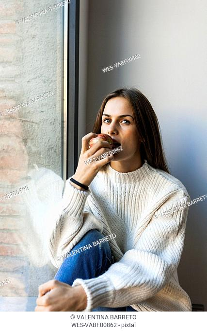 Young woman eating an apple at a window