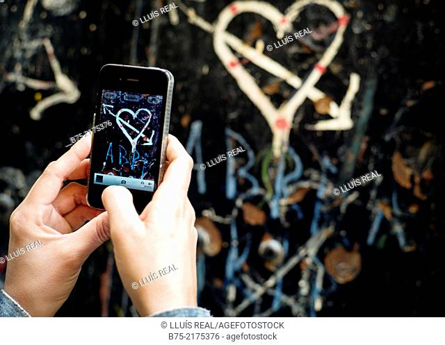 Heart with arrow painted on a wall and close-up of female hands with a phone making a photo in the Medina of Fez, Morocco, Africa