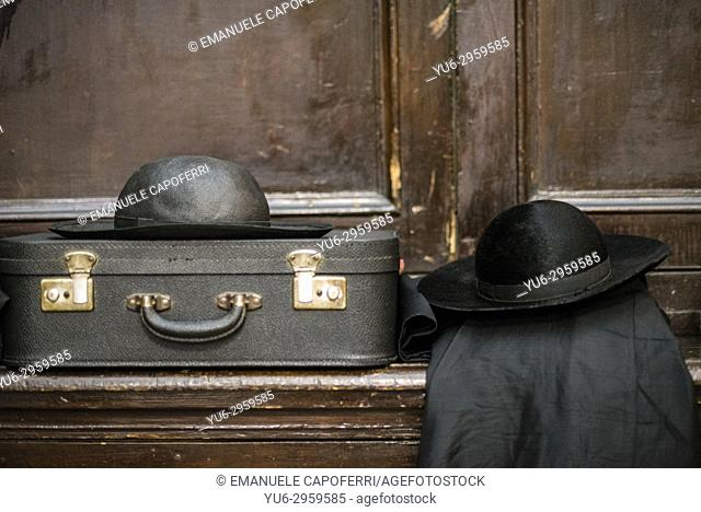Two priestly hats and an old suitcase resting on a sacristy furniture