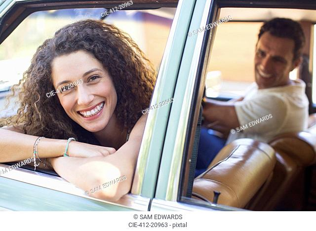 Woman relaxing on car door during car ride
