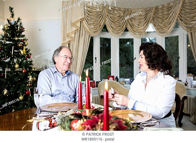 Senior couple sitting at dining table on Christmas Eve