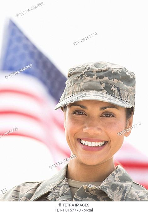 Portrait of female army soldier, American flag in background