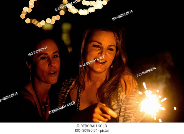 Mature female friends playing with sparkler in garden at night