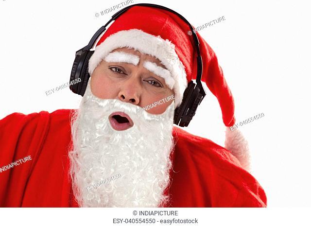 Close up of Santa Claus enjoying music over white background