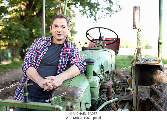 Germany, Saxony, Mature man standing by tractor, smiling