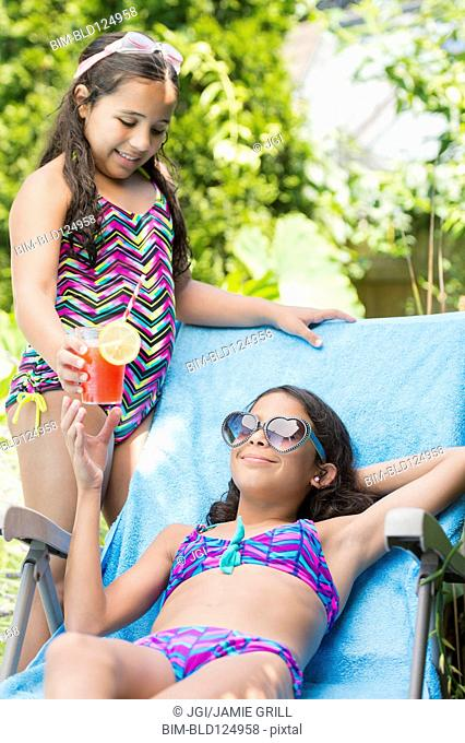 Mixed race girl serving sister juice at poolside