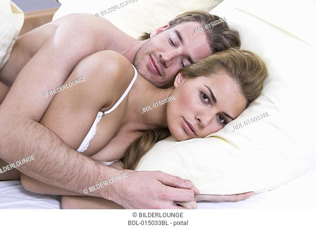 young couple lying in bed together woman looking annoyed
