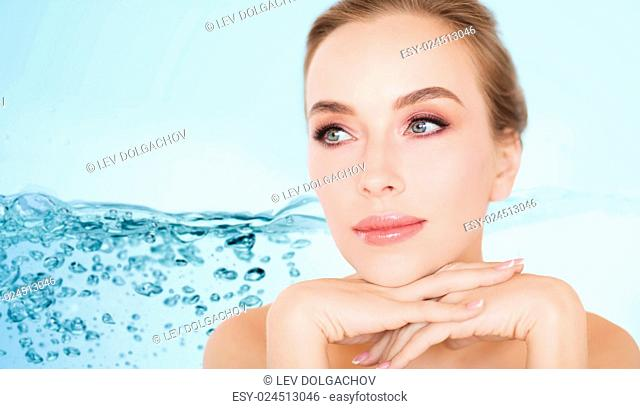 beauty, people, moisturizing and skincare concept - beautiful young woman face and hands over white background