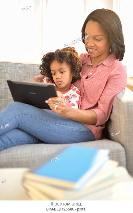Black mother and daughter using digital tablet on sofa