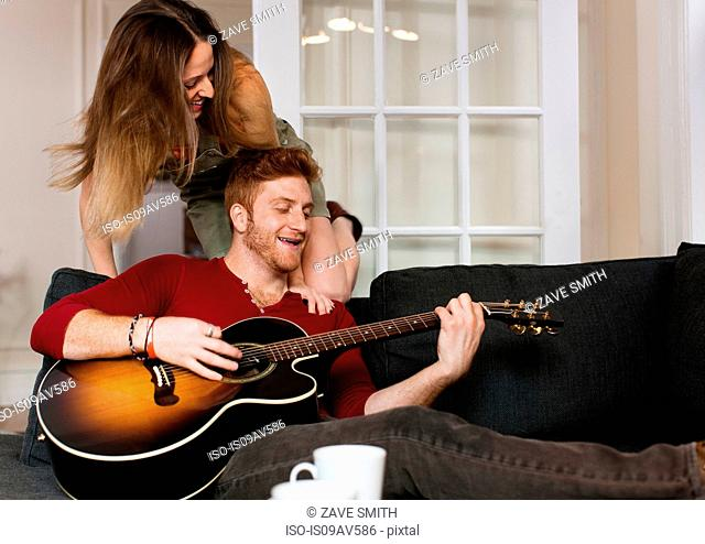 Young man sitting on sofa playing guitar to young woman smiling