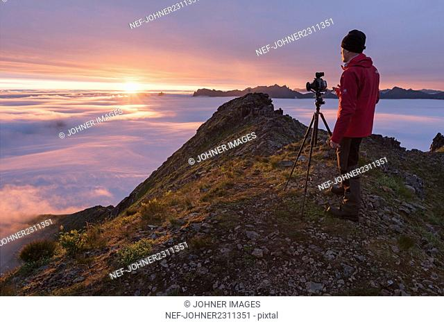 Man photographing mountains at sunrise