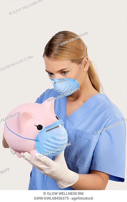 Female doctor wearing a flue mask and holding a piggy bank