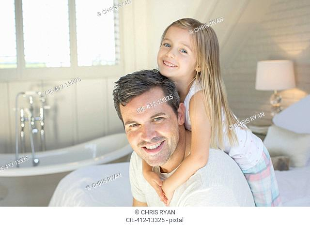 Father and daughter smiling in bedroom