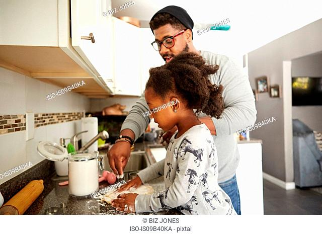 Father and daughter baking cookies together