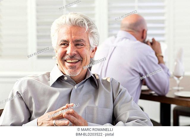 Hispanic businessman laughing in cafe