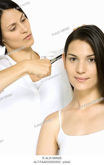 Woman having her hair cut, smiling at camera