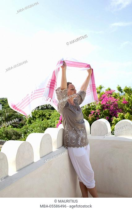 Woman on roof terrace, holding cloth, wind, summer, vacation, enjoying